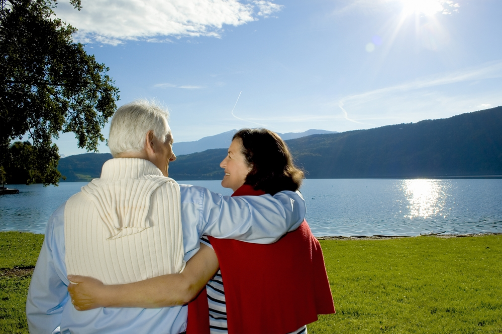Elderly couple looking at a lakeside scenery